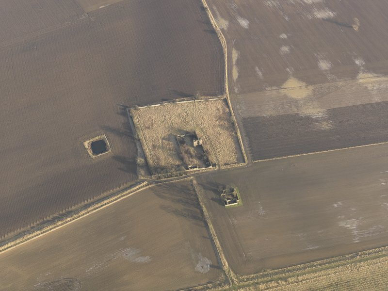 Oblique aerial view centred on the remains of the castle with the remains of the farmstead adjacent, taken from the WNW.