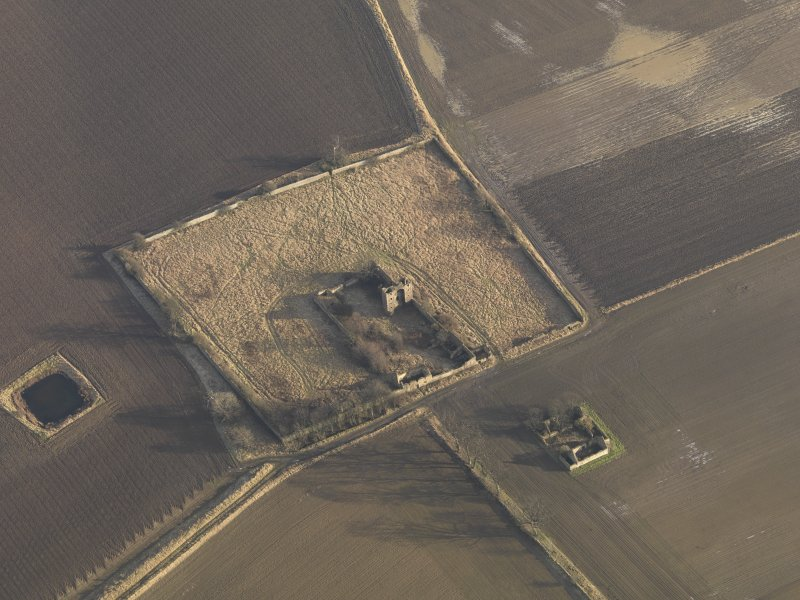 Oblique aerial view centred on the remains of the castle with the remains of the farmstead adjacent, taken from the W.