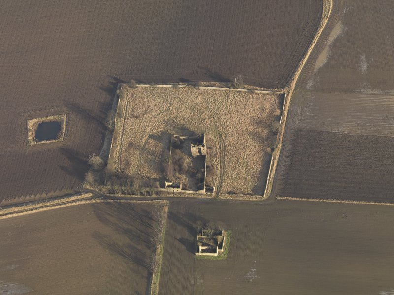 Oblique aerial view centred on the remains of the castle with the remains of the farmstead adjacent, taken from the WSW.