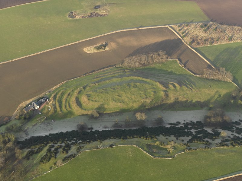 Oblique aerial view centred on the remains of the fort with the farmstead adjacent, taken from the S.