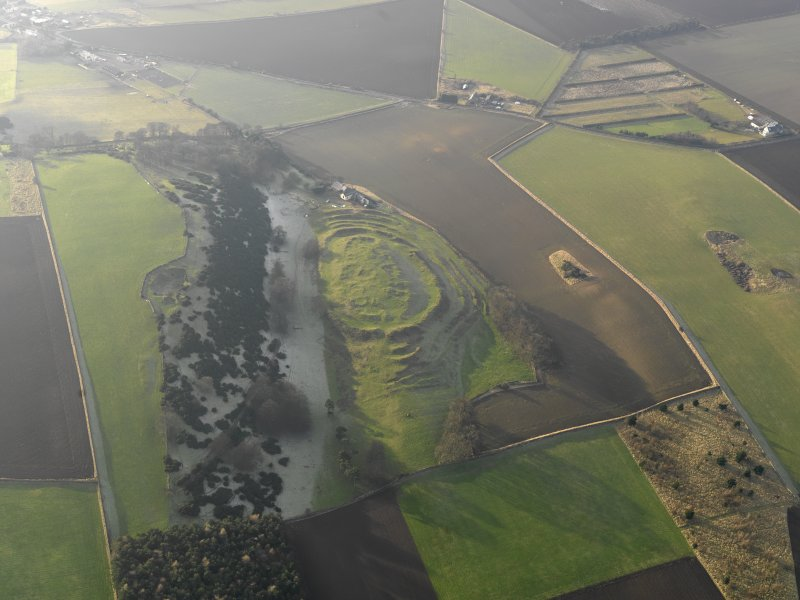 General oblique aerial view centred on the remains of the fort with the farmstead adjacent, taken from the E.