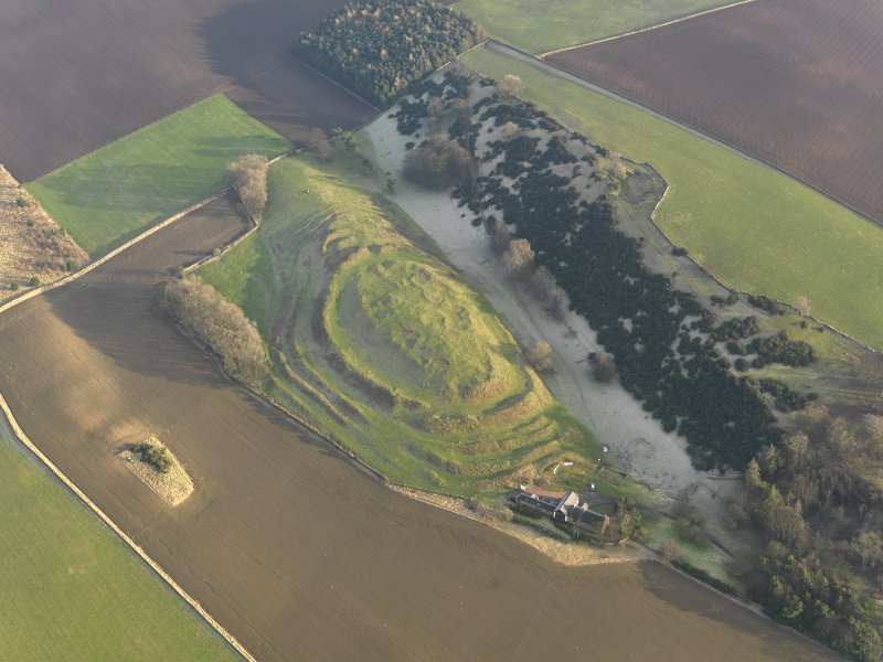 Oblique aerial view centred on the remains of the fort with the farmstead adjacent, taken from the WNW.
