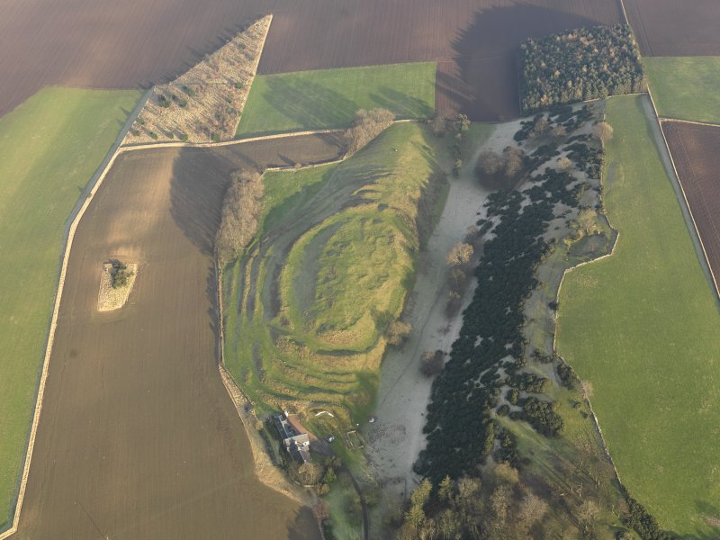 Oblique aerial view centred on the remains of the fort with the farmstead adjacent, taken from the WSW.