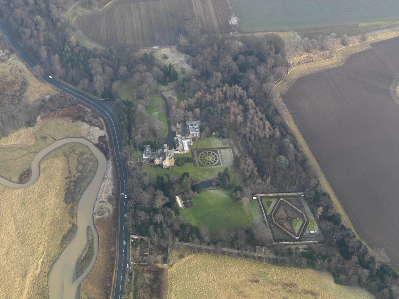Oblique aerial view centred on the country house with the gardens adjacent, taken from the W.