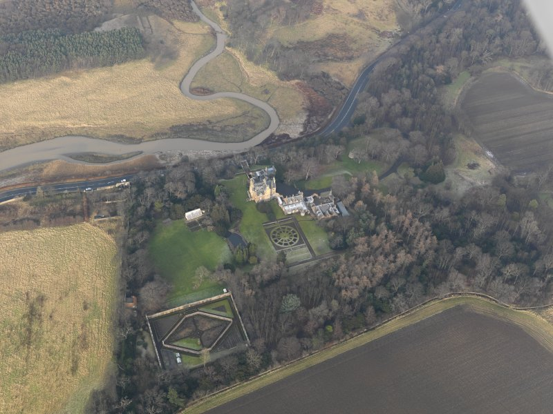 Oblique aerial view centred on the country house with the gardens adjacent, taken from the SW.