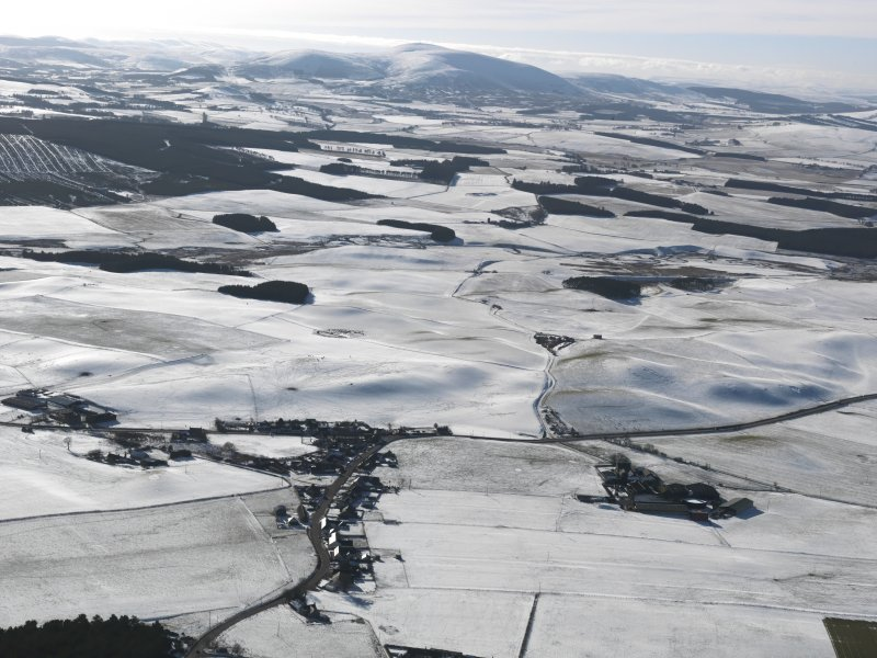 General oblique aerial view looking over the village of Newbigging towards snow-covered Tinto, taken from the NNE.