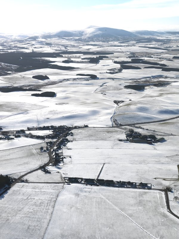 General oblique aerial view looking over the village of Newbigging towards snow-covered Tinto, taken from the North North-East.