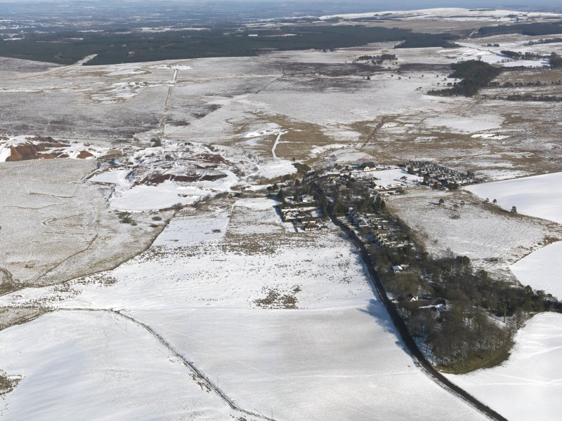 General oblique aerial view of the village and the shale oil works bings, taken from the SSW.