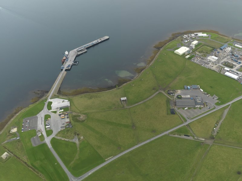 Oblique aerial view centred on part of the airfield with the ferry pier adjacent, taken from the  NW.