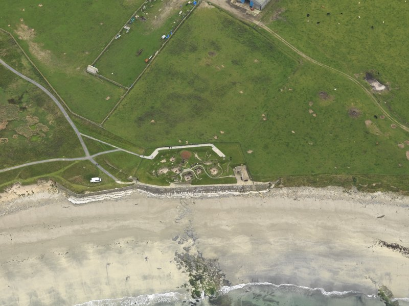 Oblique aerial view centred on the prehistoric settlement, taken from the N.