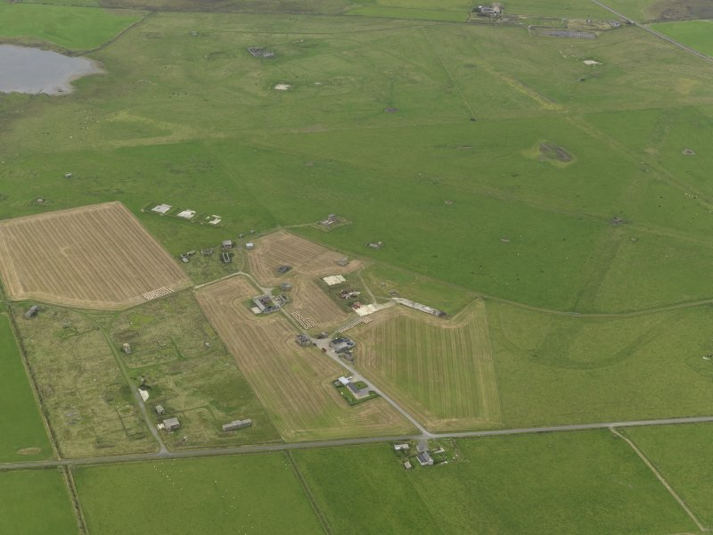 Oblique aerial view centred on the technical site with the airfield adjacent, taken from the S.