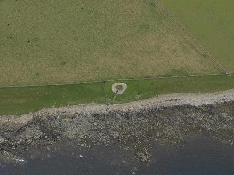 Oblique aerial view centred on the remains of the chambered cairn, taken from the ESE.