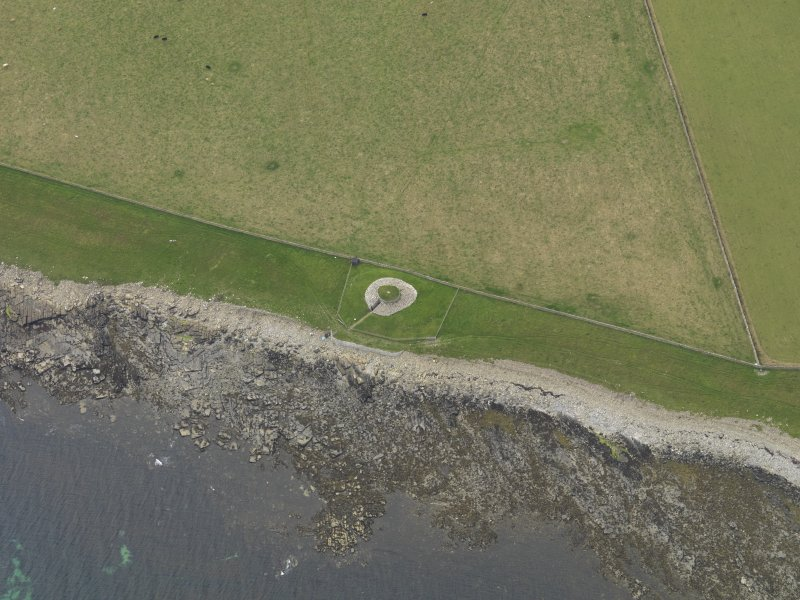 Oblique aerial view centred on the remains of the chambered cairn, taken from the ENE.