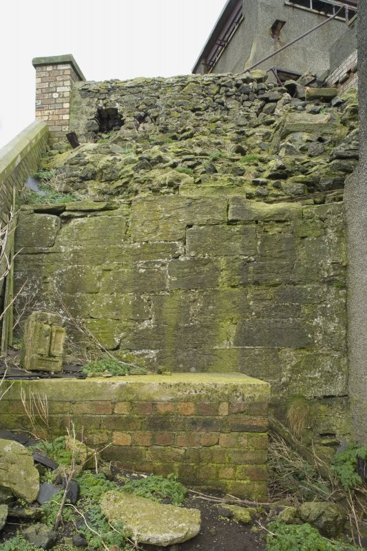 Detail of a section of possible 16th century wall showing rubble infill and facing blocks with 20th century brick platform, taken from SW.
