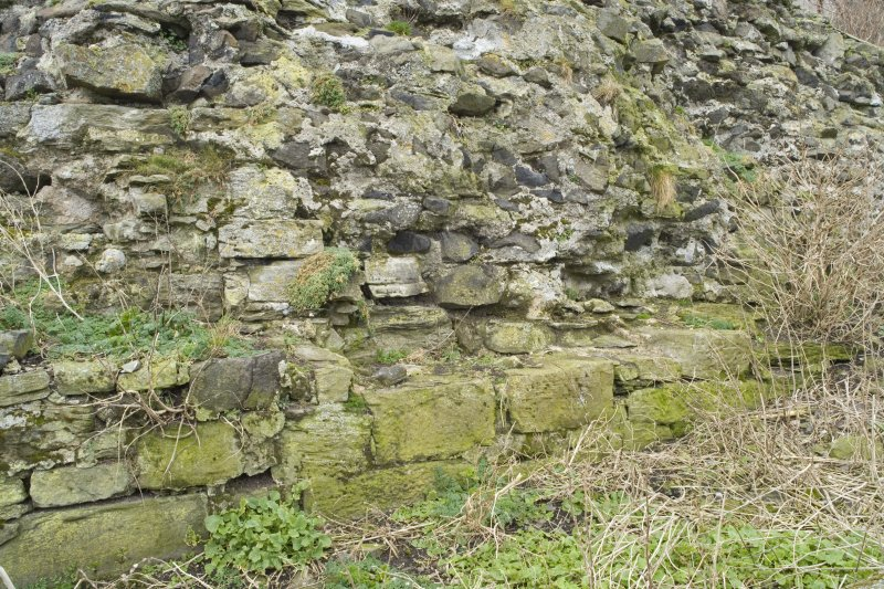 Detail of surviving section of 16th century wall showing rubble infilling and lower two course of faced blocks from SE.