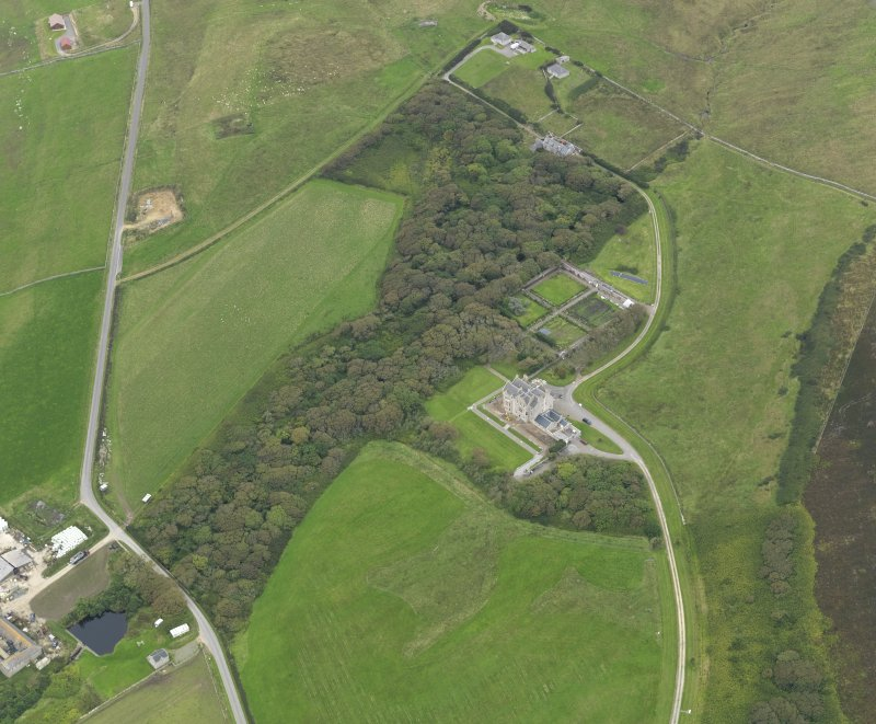 Oblique aerial view centred on the house and gardens with the remains of the chambered cairn adjacent, taken from the SE.