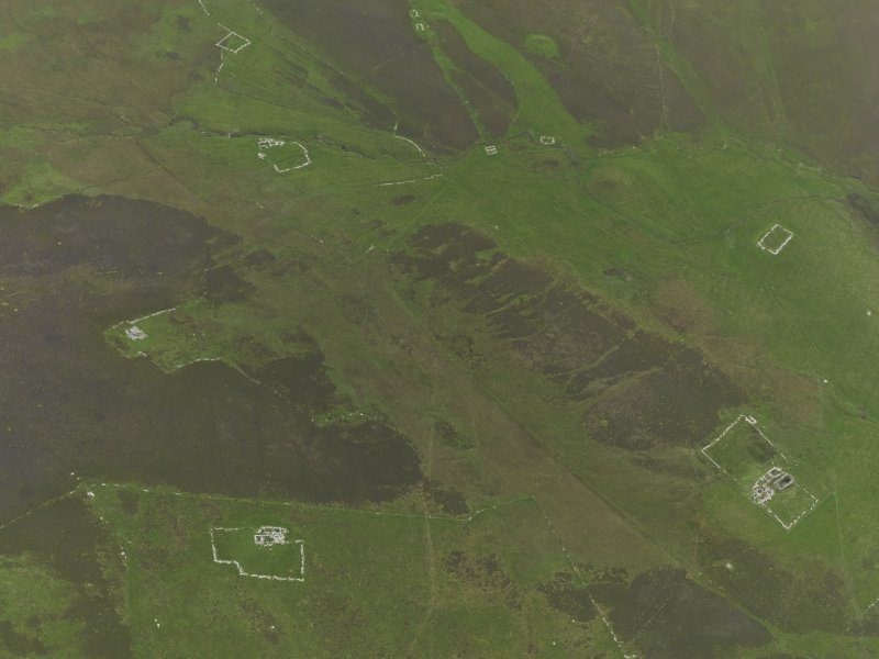 Oblique aerial view centred on the remains of the farmsteads, field systems and head dykes, taken from the N.