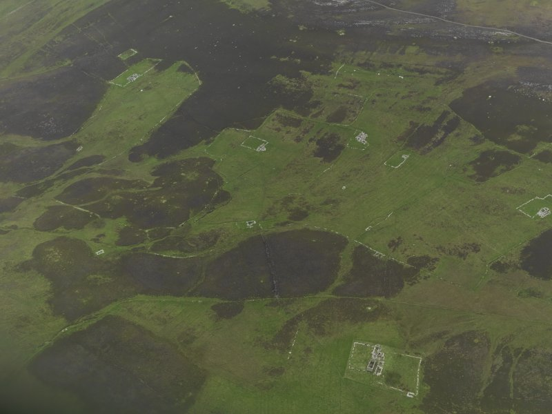 Oblique aerial view centred on the remains of the farmsteads, field systems and head dykes, taken from the SW.