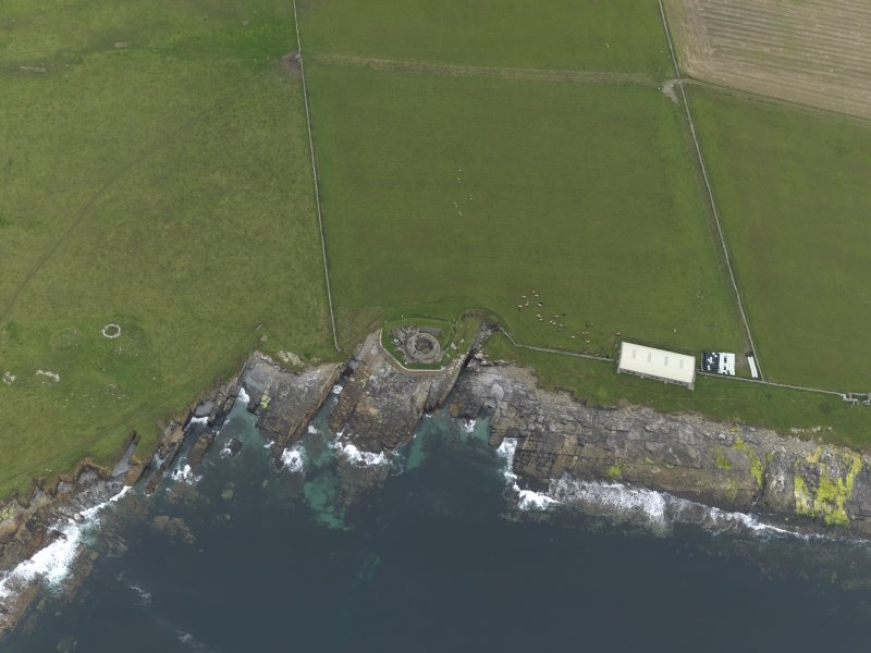 Oblique aerial view centred on the remains of the broch and settlement, with the remains of the broch, building and shed covering the chambered cairn adjacent, taken from the SW.