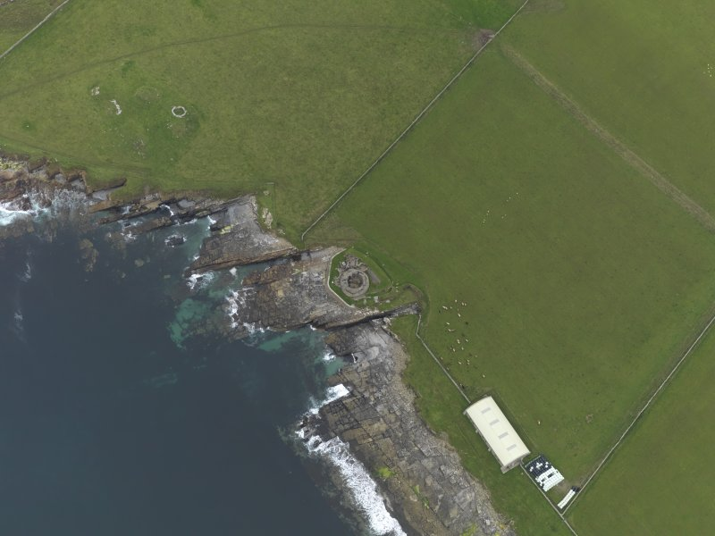Oblique aerial view centred on the remains of the broch and settlement, with the remains of the broch, building and shed covering the chambered cairn adjacent, taken from the S.