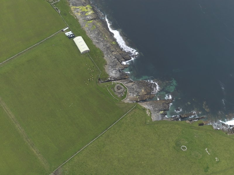 Oblique aerial view centred on the remains of the broch and settlement, with the remains of the broch, building and shed covering the chambered cairn adjacent, taken from the N.