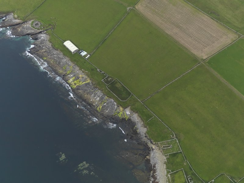 Oblique aerial view of the remains of the brochs, settlement, church, hall, tower house and shed covering the chambered cairn, taken from the S.