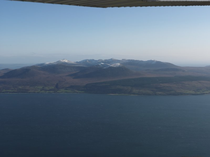 Distant general oblique aerial view looking across the snow-dusted tops of Arran, taken from the W.