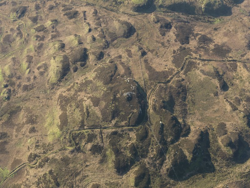 Oblique aerial view centred on the remains of the fort and possible cairn on Ranachan Hill, taken from the NNE.