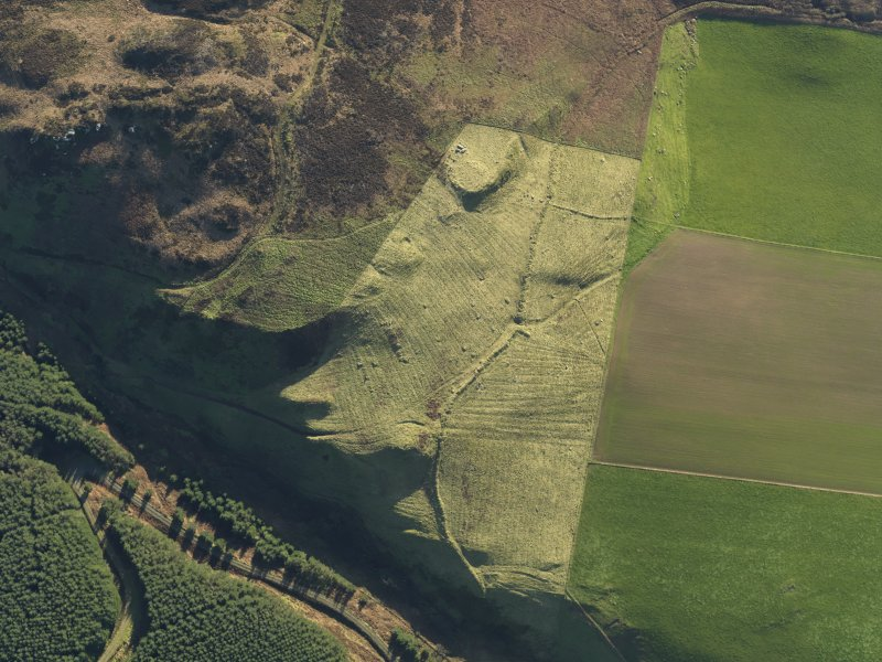 Oblique aerial view centred on the remains of the dun, field banks and rig at Balnagleck Farm on the Mull of Kintyre, taken from the NNW.