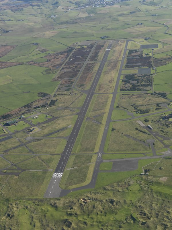 Oblique aerial view of Machrihanish Airfield looking along the runway, taken from the WNW.