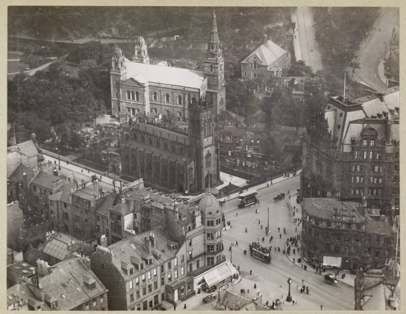 Oblique aerial view from the northwest of the West End of Princes Street, Edinburgh, showing St John's Church, St Cuthbert's Church, Maules Store (now Frasers) and part of the Caledonian Hotel.