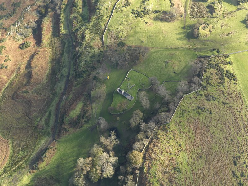 Oblique aerial view centred on ruin of the church and the burial ground, taken from the N.