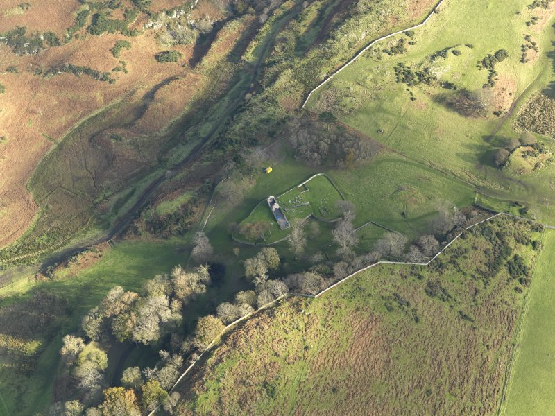 Oblique aerial view centred on the ruin of the church and the burial ground, taken from the NW.