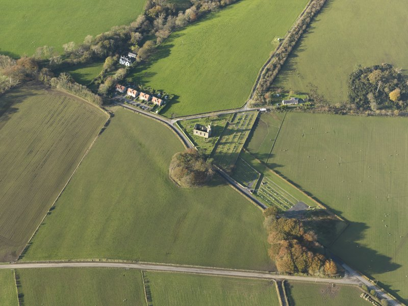 Oblique aerial view centred on the church and the remains of the earthwork, taken from the SSE.