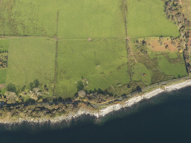 General aerial oblique view centred on the remains of the chambered cairn, taken from the SW.