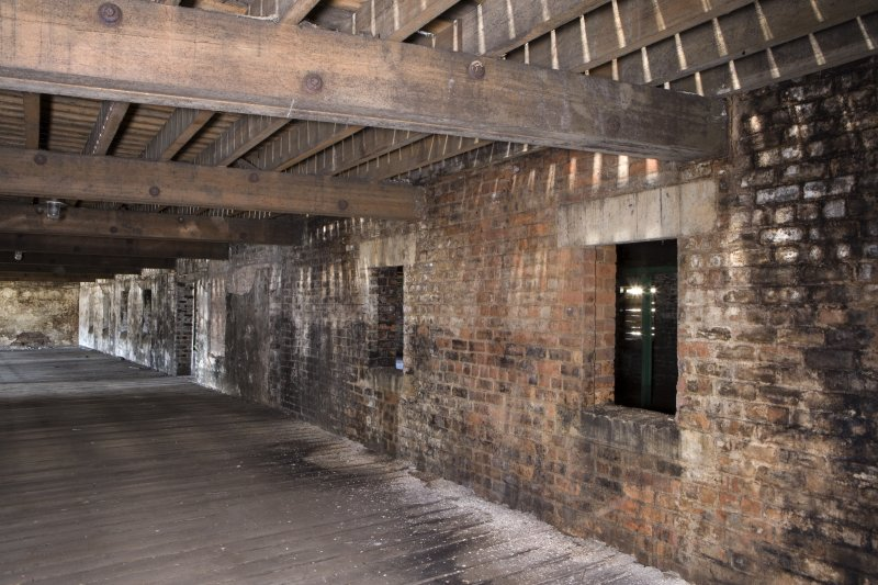 Interior view, looking along the S side of the dividing wall within the first floor of bonded warehouse (west section) at the former Rosebank Distillery.
