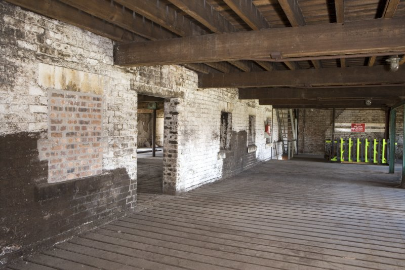 Interior view of the bonded warehouse (west section) at former Rosebank Distillery, looking along the N side of the dividing wall at first floor, towards the barrel hoist.