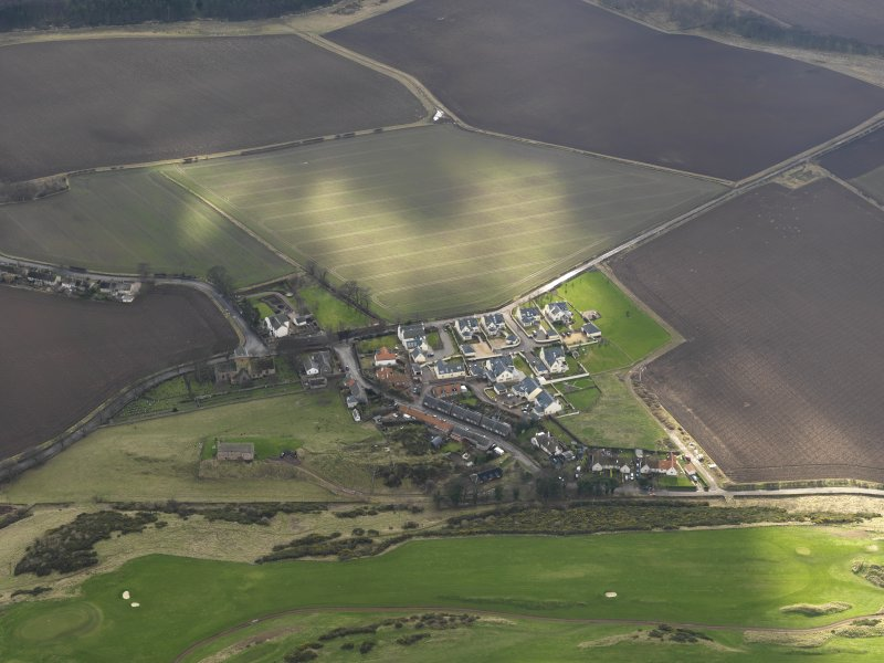 Oblique aerial view centred on the village with the parish church adjacent, taken from the N.