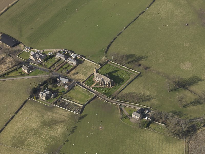 Oblique aerial view centred on the village with the church adjacent, taken from the SE.