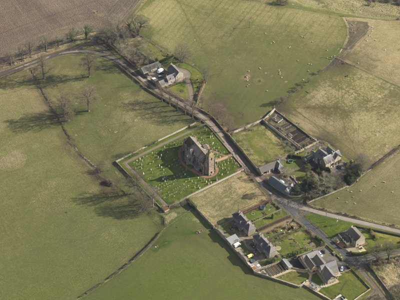 Oblique aerial view centred on the village with the church adjacent, taken from the WNW.
