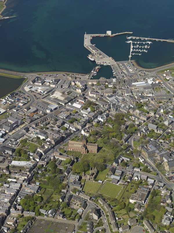 General oblique aerial view of Kirkwall centred on St Magnus' Cathedral with the harbour beyond, taken from the S.