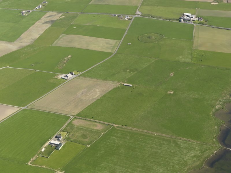 General oblique aerial view centred on the soilmarks of the enclosure at Overbigging with Maes Howe beyond, taken from the WNW.