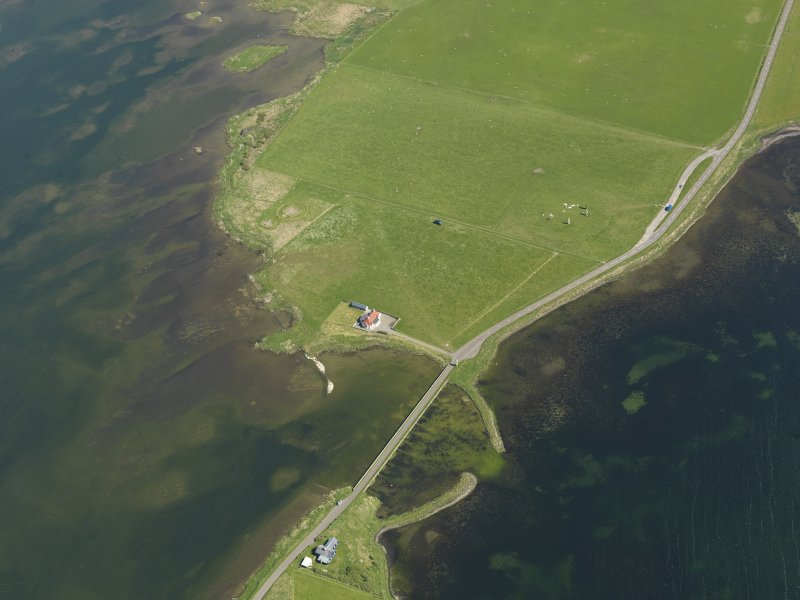 Oblique aerial view centred on the Bridge of Brodgar with The Watch Stone, the Stones of Stenness and the Barnhouse settlement adjacent, taken from the WNW.