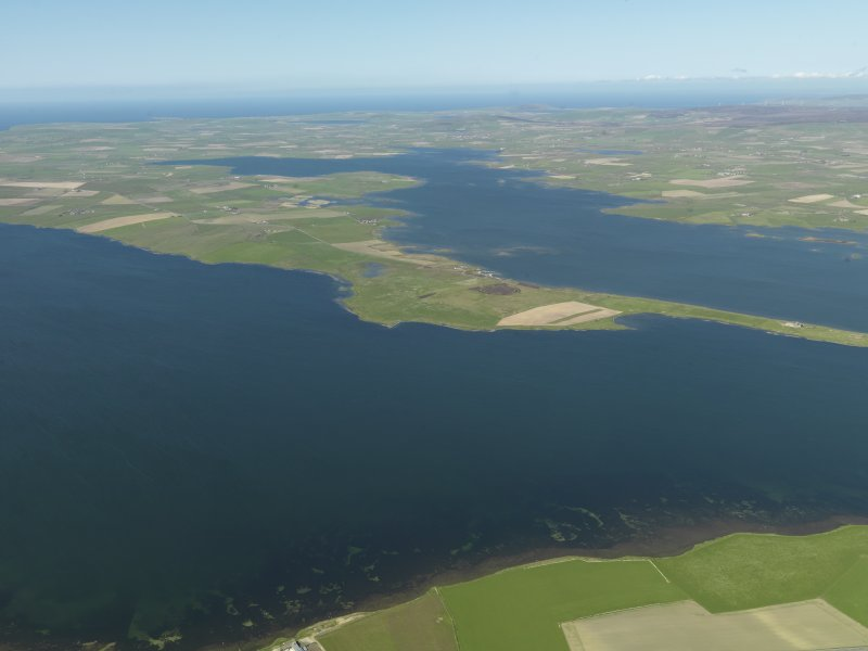 General oblique aerial view looking across the Loch of Stenness towards the Ring of Brodgar with the Loch of Harray beyond, taken from the S.