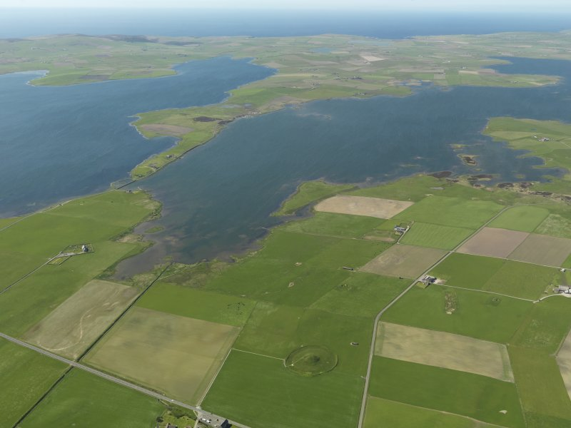 Oblique aerial view with Maes Howe in the foreground looking towards the Loch of Harray with the Ring of Brodgar beyond, taken from the NE.