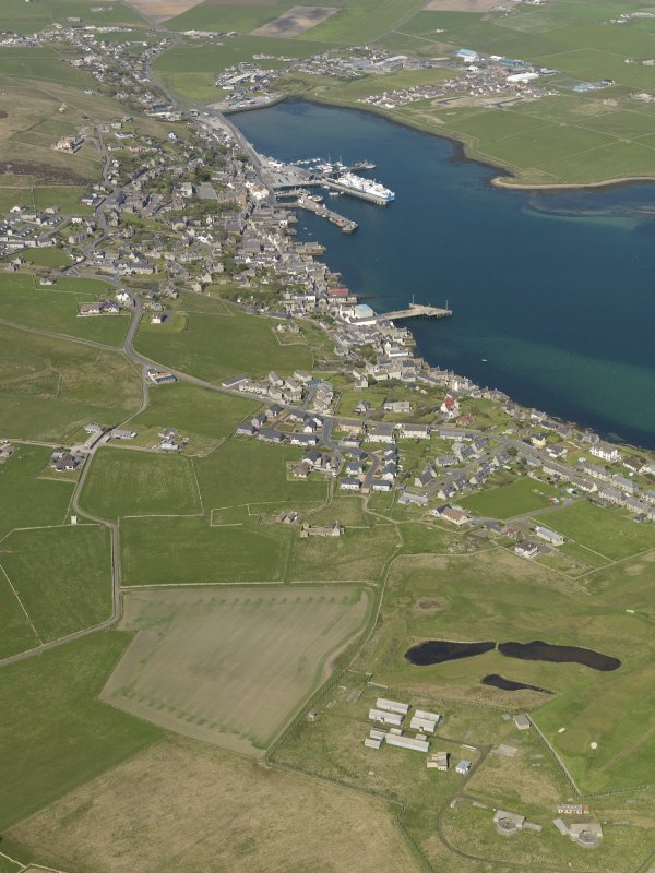 General oblique aerial view of Stromness with the Ness Battery in the foreground, taken from the WSW.
