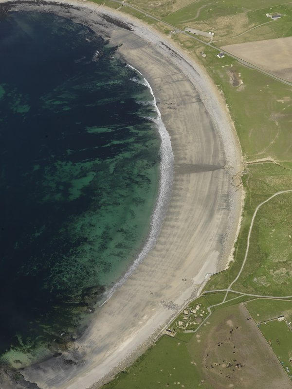 Oblique aerial view of Skara Brae looking along the beach in the bail of Skaill, taken from the SW.