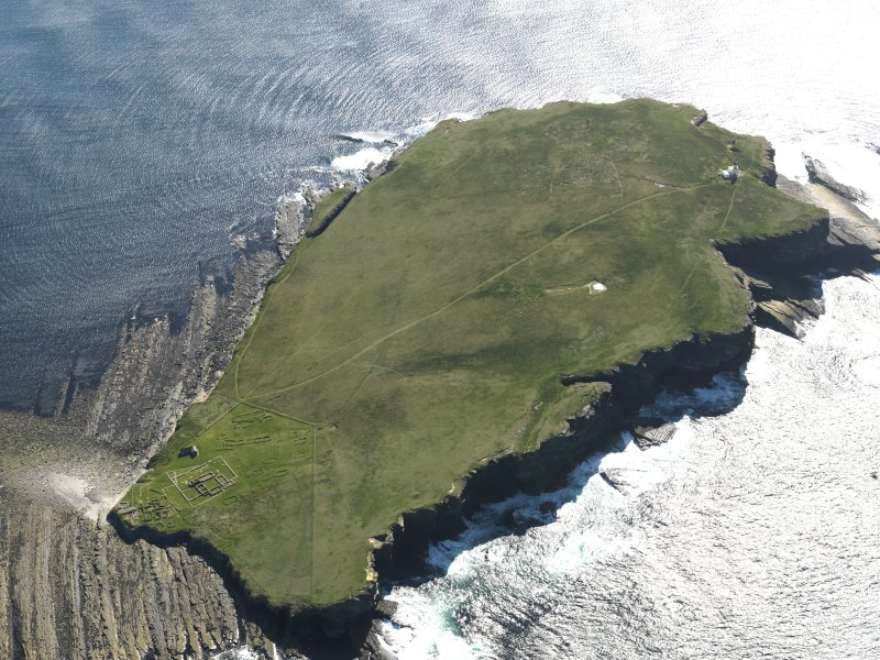 General oblique aerial view of the Brough of Birsay with the lighthouse to the top right and the monastic settlement to the bottom left, taken from the NE.