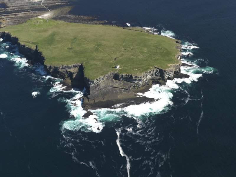 General oblique aerial view of the Brough of Birsay centred on the lighthouse, with the chapel and settlement in the distance, taken from the NW.