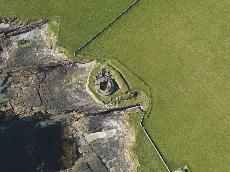 Oblique aerial view centred on Midhowe broch, Rousay, taken from the SSW.